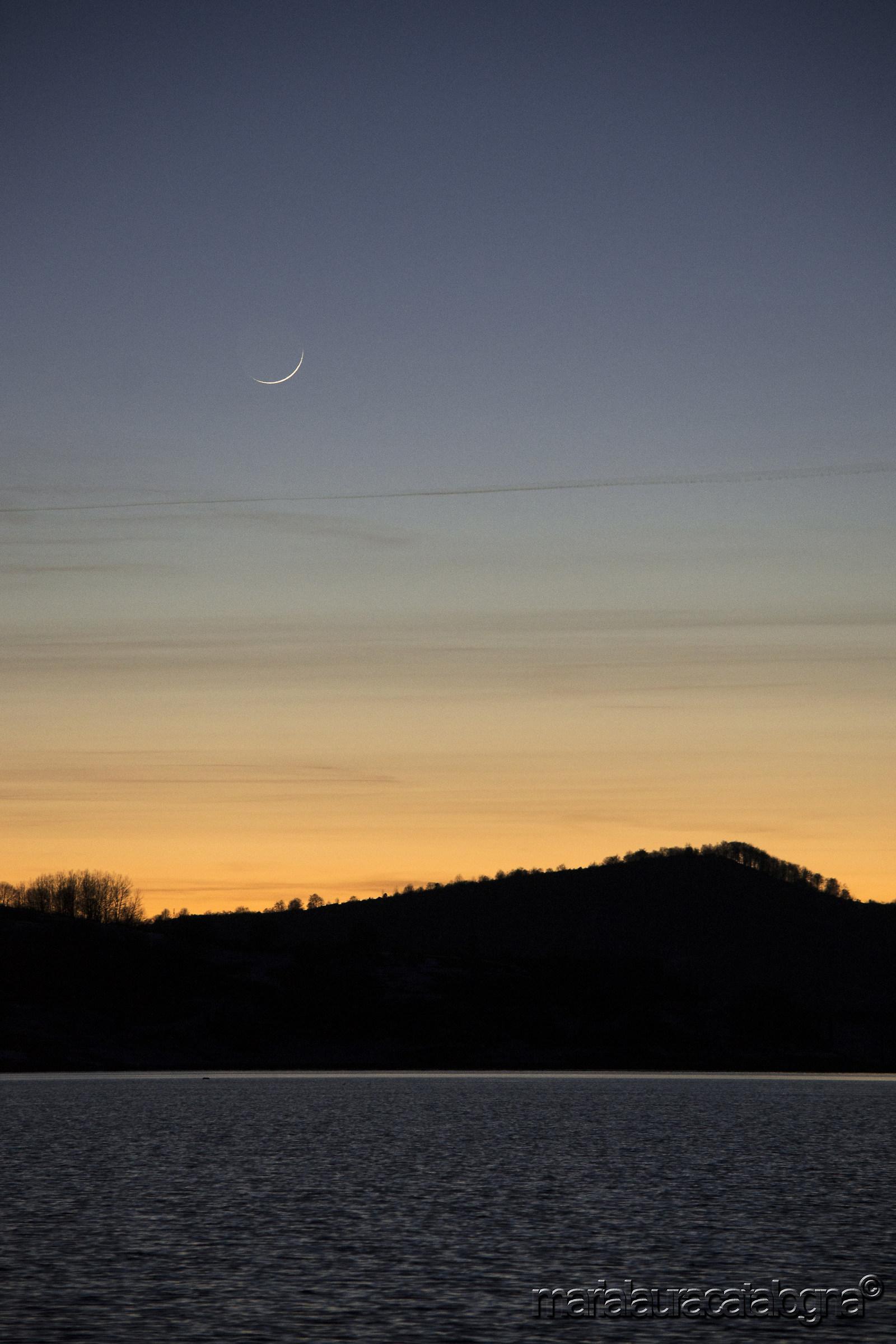 Campotosto lake at sunset and thin waning moon...