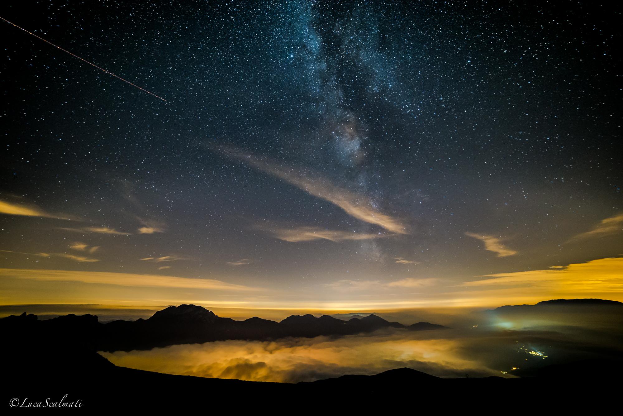 Via Lattea che sembra nascere dalle luci della valle...