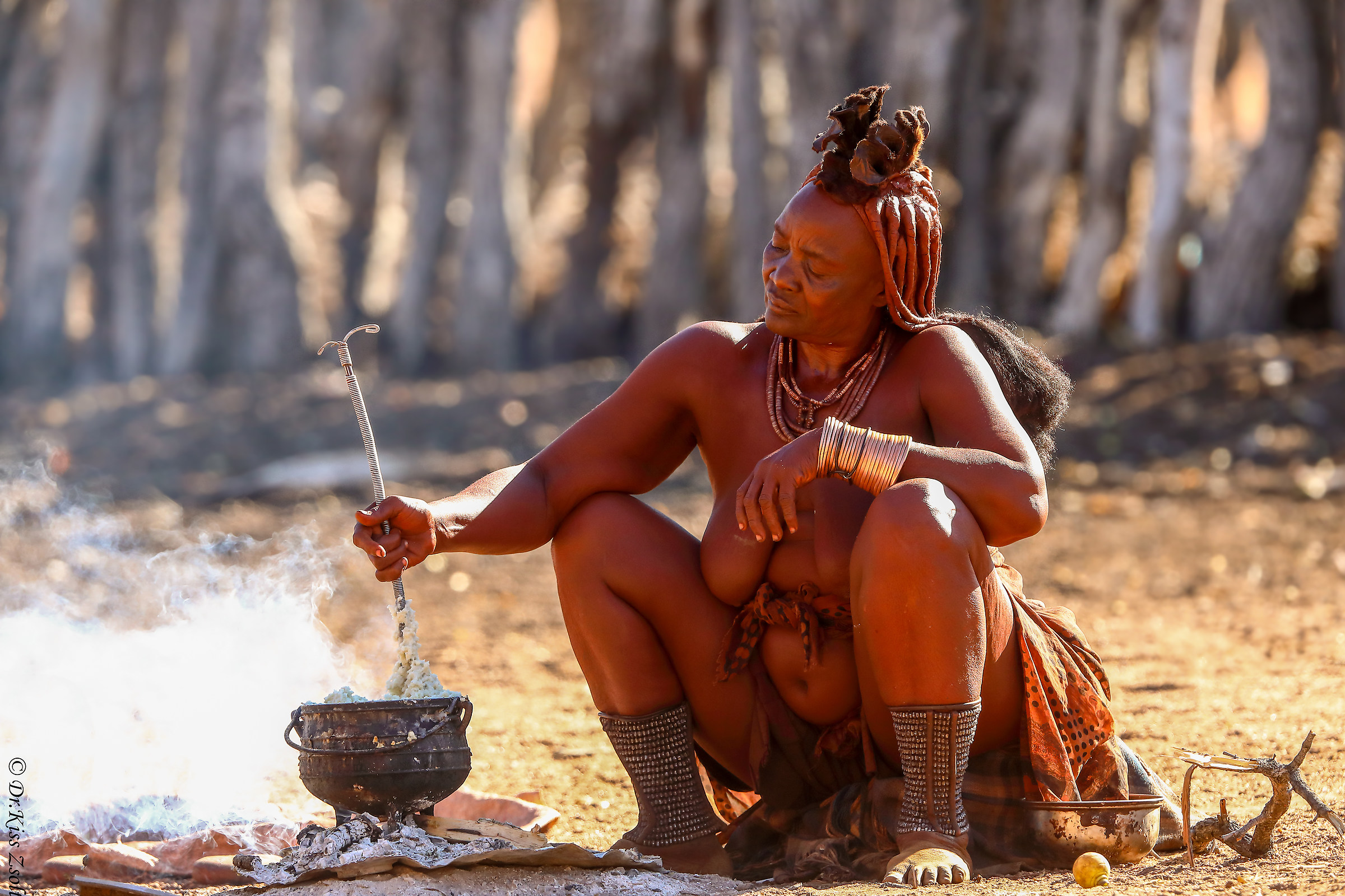 Elderly himba woman, cooking her meal...
