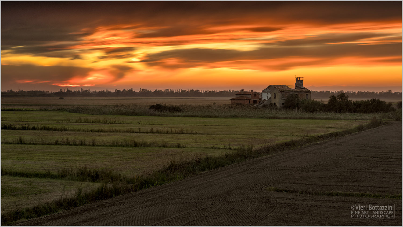 Vivid sunset on crumbling farm...